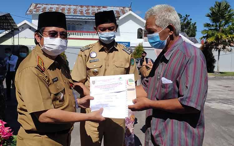 Kepala Dinas Pendapatan Daerah (Dispenda) Provinsi Kalteng, Kaspinor saat menyerahkan BST secara simbolis kepada ada keluarga penerima manfaat