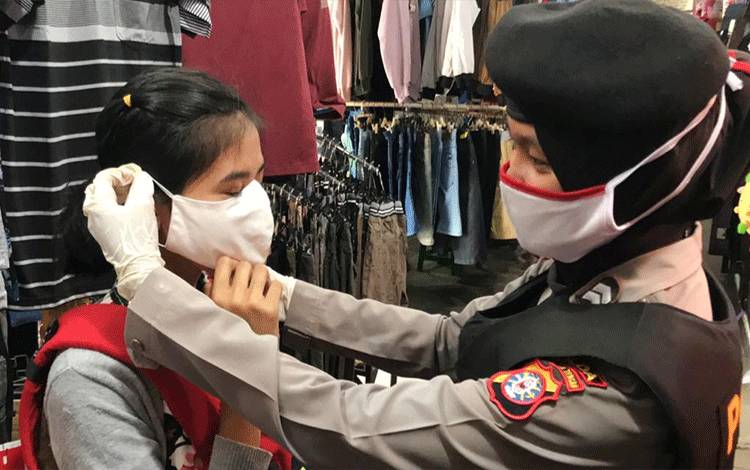 Polwan Ditsamapta Polda Kalteng saat memasangkan masker kepada pedagang pasar.