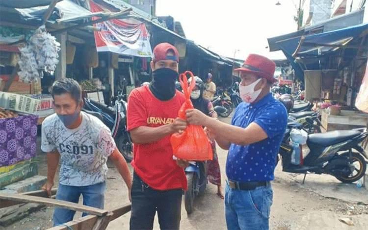 Ketua Pasar Besar, Hamidan (kaos biru) membagikan paket sembako kepada buruh angkut.
