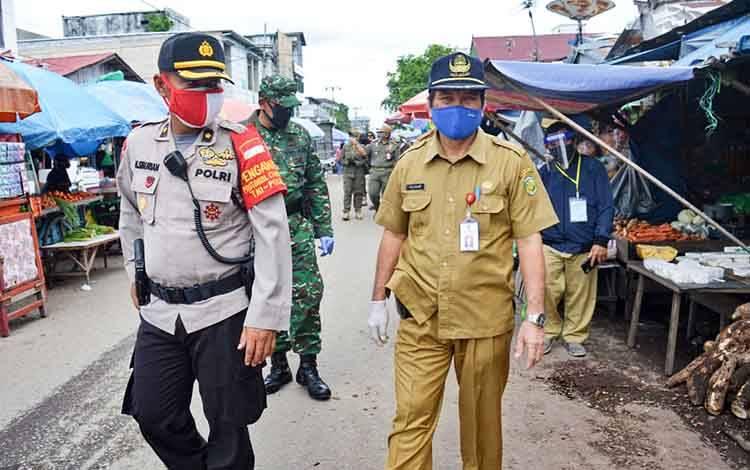 Kabagops Polresta Palangka Raya, Kompol Hemat Siburian bersama unsur pemerintah dan TNI melakukan pemantauan sekaligus menyosialisasikan protokol kesehatan di Pasar Besar, Selasa 23 Juni 2020