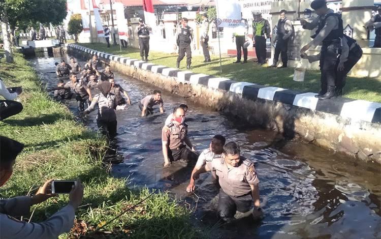 Puluhan personel Polres Seruyan saat melaksanakan tradisi menceburkan diri ke parit yang ada di halaman Mapolres Seruyan, usai upacara kenaikan pangkat.