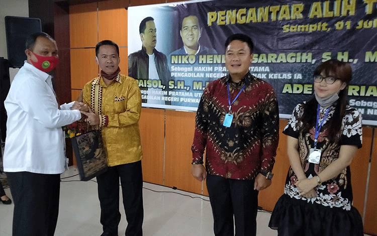 Pengantar tugas hakim Pengadilan Negeri Sampit, Ketua Pengadilan Negeri SampitH.AFJoko Sutrisno saat memberikan cindera mata.