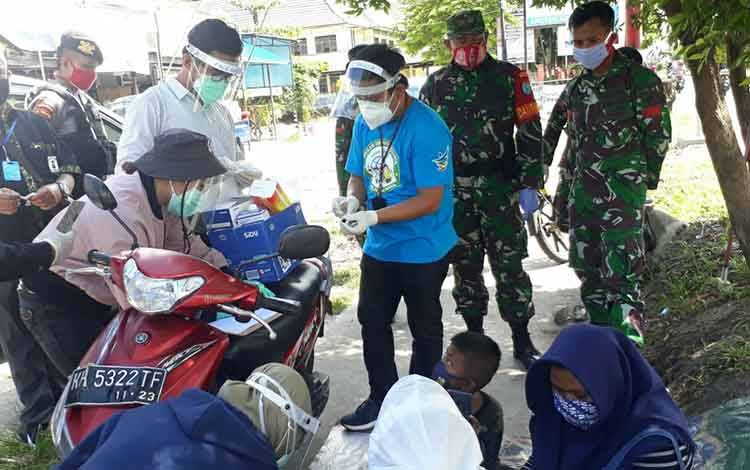 Danramil 1016-01 Pahandut Mayor Inf Heru Widodo bersama Babinsa Serka Ilham mendampingi pelaksanaan rapid test pedagang Pasar Kameloh, Rabu 1 Juli 2020