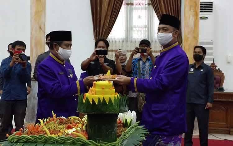 Bupati Sukamara, Windu Subagio saat menyerahkan pptongan tumpeng kepada tokoh pemekaran Kabupaten Sukamara.