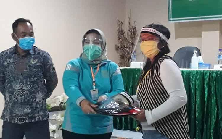 Bupati Kobar Hj Nurhidayah memberikan kartu peserta, sebagai tanda dimulainya pelatihan tata kelola destinasi wisata.