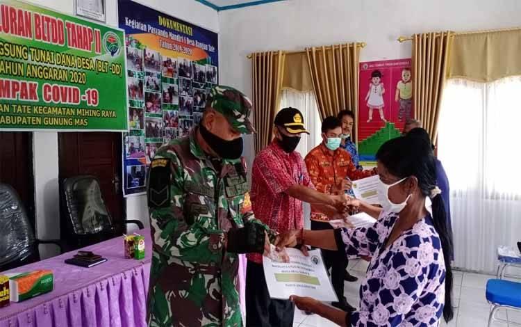 Babinsa Koramil 1016-03 Sepang Desa Rangan Tate, Serka Helprit membantu menyalurkan bantuan BLT DD