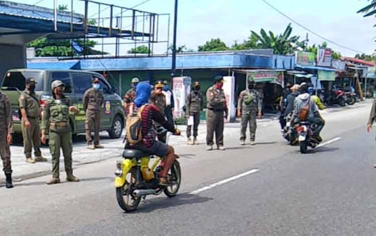 Anggota Satpol PP Kota Palangka Raya saat melakukan penertiban protokol kesehatan dalam penggunaan masker terhadap pengguna jalan di kawasan Jalan Murjani, Jumat 3 Juni 2020.