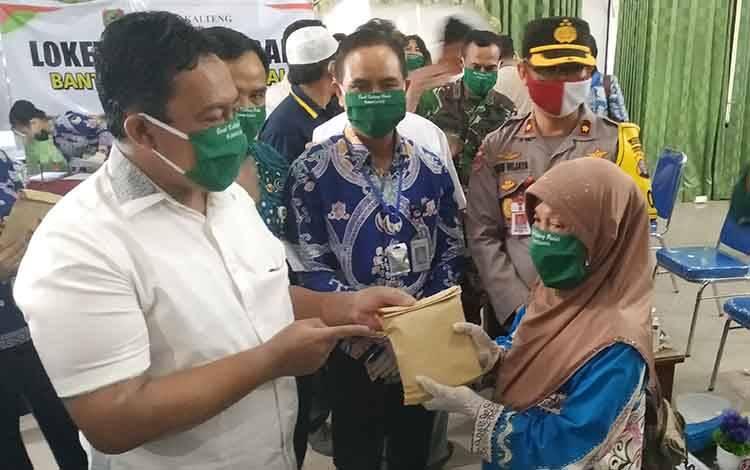 Bupati Pulang Pisau, Edy Pratowo menyerahkan bantuan uang pribadi dari Gubernur Kalimantan Tengah kepada warga.