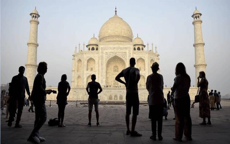 Pengunjung melihat monumen cinta India yang terkenal dengan nama Taj Mahal, di Agra, India, 22 Maret 2018. Monumen pada abad ke-17 ini menjadi daya tarik wisata terbesar di India, dengan sekitar 3 juta orang berkunjung setiap tahun. (AP Photo/R.S. Iyer)