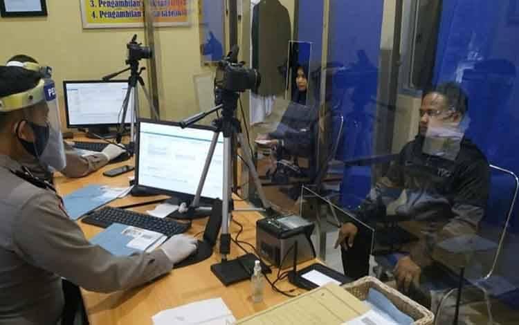 Petugas Satpas SIM Satlantas Polres Kobar perketat protokol kesehatan saat mengambil foto pemohon SIM.