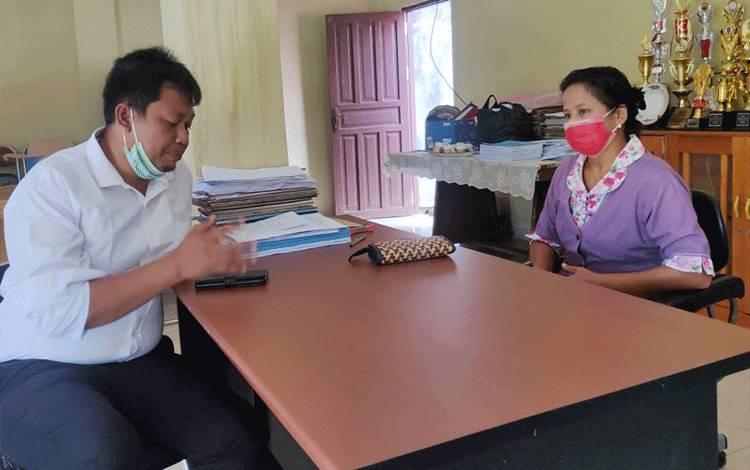 Anggota Satintelkam Polres Katingan berbincang dengan Pendeta Rita Mariane Baun.