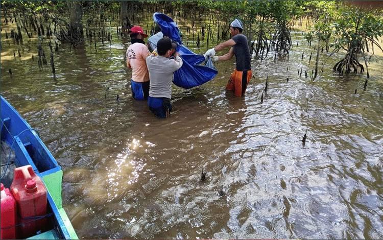 Sejumlah warga dan aparat kepolisian saat melakukan evakuasi penemuan mayat mengapung di Sungai Pasir, Senin, 6 Juli 2020.