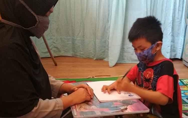 Muliya memberikan pendampingan pembelajaran pada anak TK yang belajar dari rumah selama pandemi Covid-19 ini.