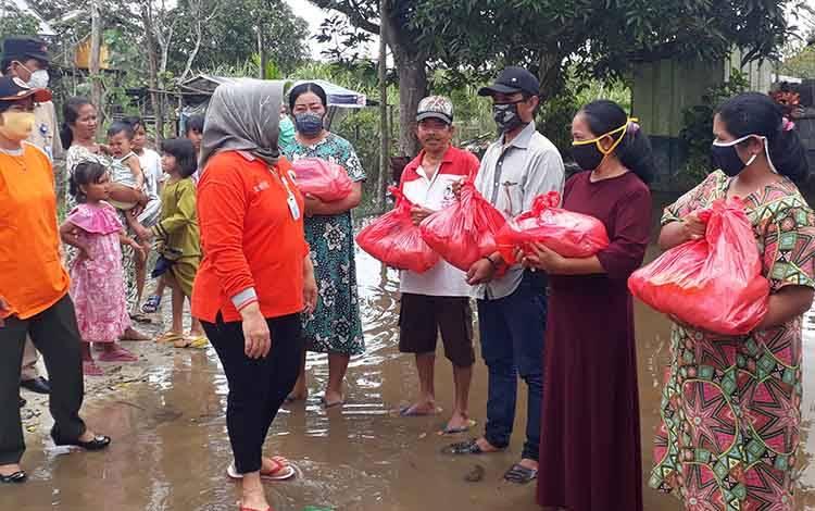 Bupati Kobar Hj Nurhidayah saat menyalurkan bantuan ke warga terdampak banjir. Tercatat ada 3 Kecamatan di Kobar terdampak musibah banjir.