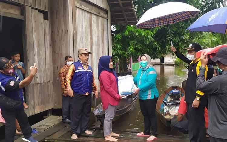 Bupati Kobar Hj Nurhidayah saat menyalurkan bantuan sosial korban banjir.