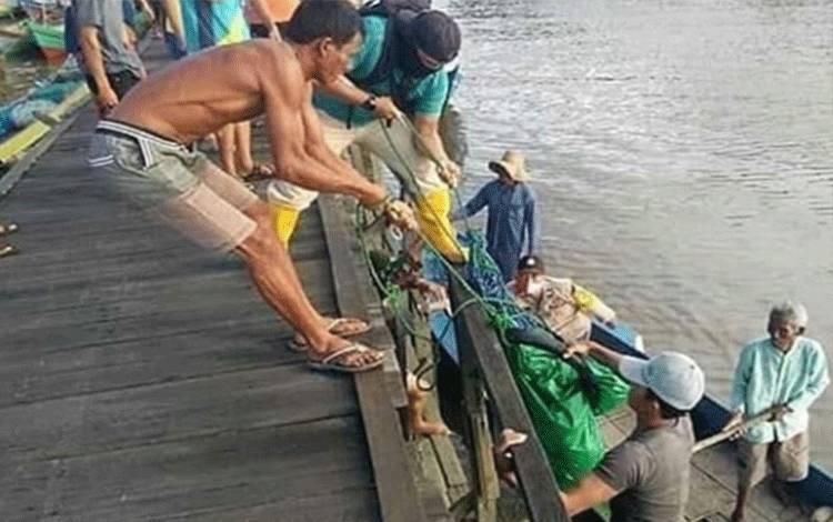 Sejumlah warga saat mengevakuasi mayat laki-laki yang ditemukan mengapung di Sungai Pasir.