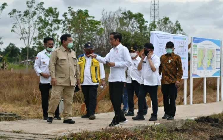 Presiden Joko Widodo berbincang dengan Menteri Pertahanan, Prabowo Subianto saat meninjau lokasi lahan food estate di Kalimantan Tengah.