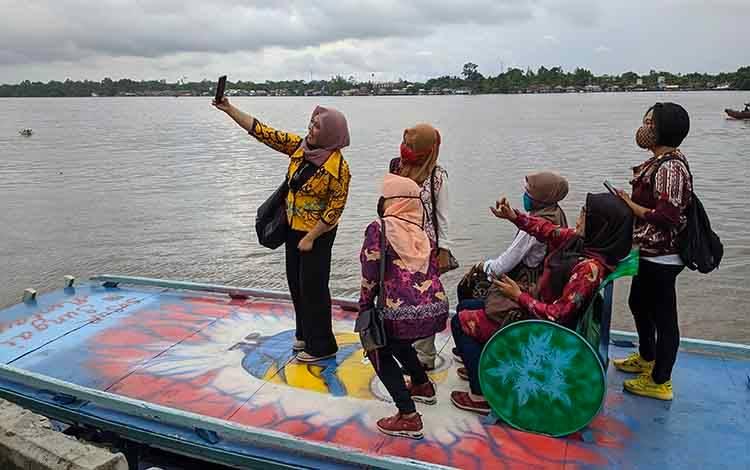 Sejumlah warga Kotim saat berselfie saat melakukan wisata susur sungai. Bupati Minta Disbudpar bantu percantik kelotok untuk kebutuhan wisata.