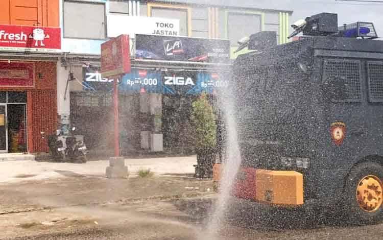 Mobil AWC Ditsamapta Polda Kalteng saat melakukan penyemprotan cairan disinfektan di kawasan pertokoan, Sabtu 11 Juli 2020.