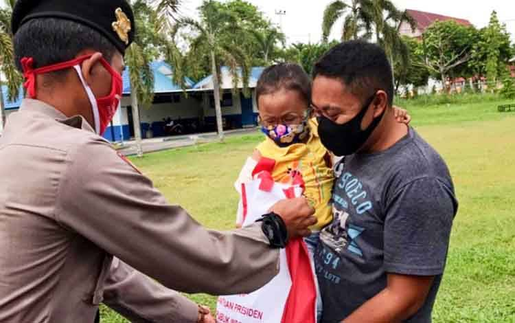 Anggota Ditsamapta Polda Kalteng saat memberikan bantuan berupa sembako kepada masyarakat terdampak covid-19 di sekitar Jalan Yos Sudarso Kota Palangka Raya, Sabtu 11 Juli 2020.