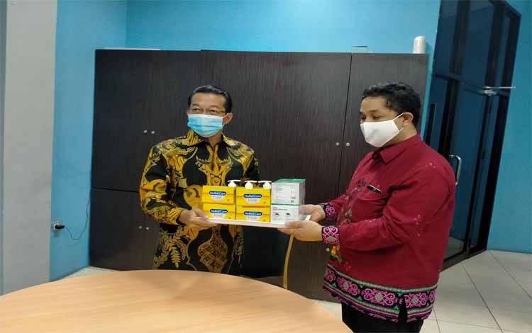 Bupati Murung Raya, Perdie M Yoseph menyerahkan bantuan masker dan vitamin kepada Pemred Palangka Post, Harris Sadikin, Sabtu 11 Juli 2020