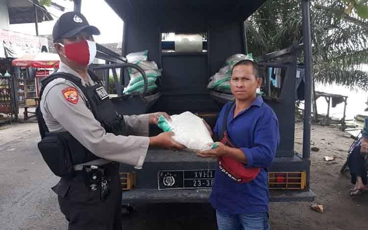 Personel Polsek Hanau menyerahkan bantuan beras untuk warga kurang mampu terdampak Covid-19