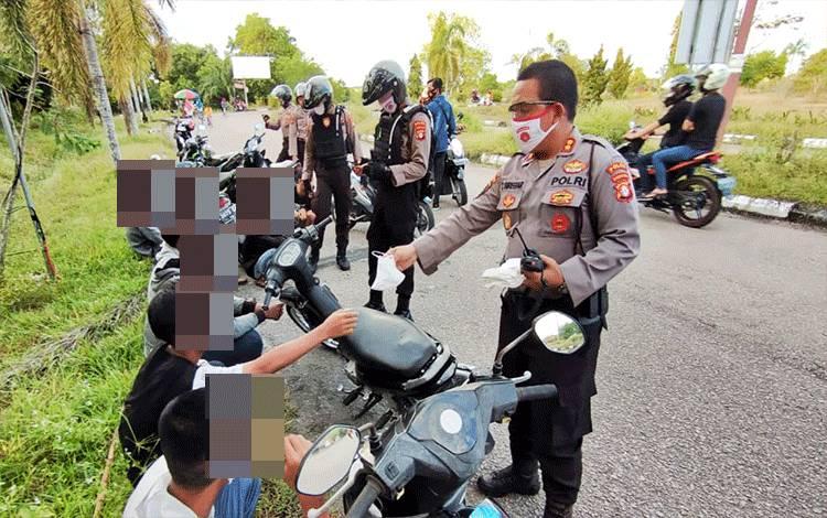 Wakil Direktur Samapta Polda Kalteng AKBP Timbul RK Siregar saat memberikan masker kepada para remaja putera.