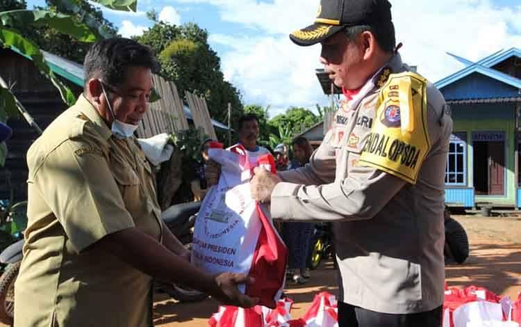 Kepala Biro Operasional atau Karoops Polda Kalteng Kombes Pol Andreas Wayan Wisaksono secara simbolis memberikan bantuan sembako kepada warga terdampak banjir di Tumbang Samba.