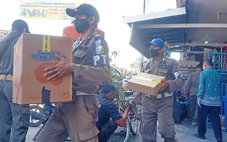 Petugas mengangkut puluhan dus berisi obat dari Apotik Manjur wilayah Pasar Besar, Kota Palangka Raya, Kamis 16 Juli 2020