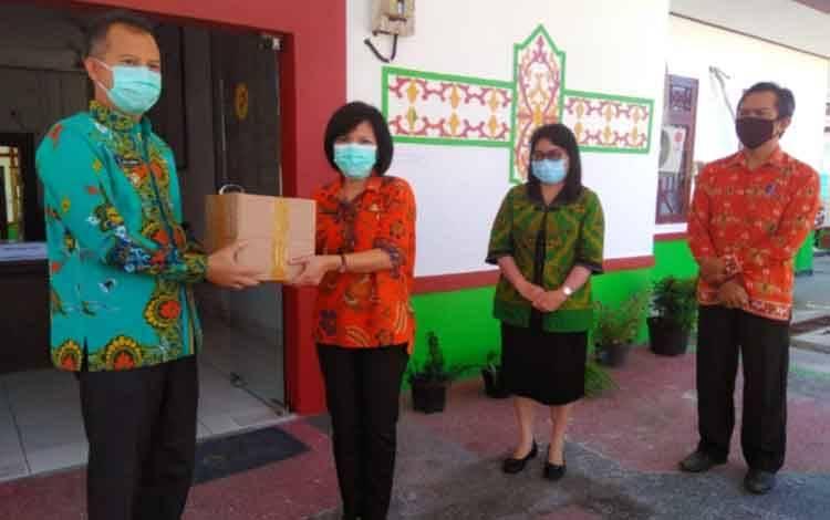 Bupati Gunung Mas, Jaya S Monong saat menyerahkan obat herbal secara simbolis kepada Kepala Dinkes, dr Maria Efianti, Kamis, 16 Juli 2020.