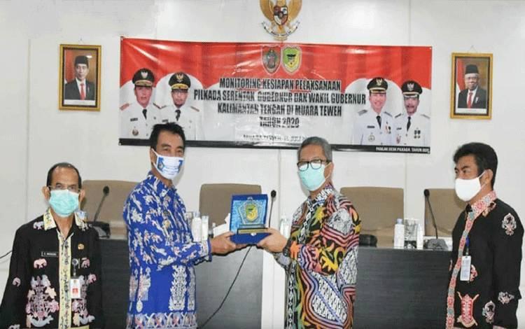 Wakil BUpati Barito Utara, Sugianto Panala Putra ketika menyerahkan plakat kabupaten kepada Tim Desk Pilkada Kalteng yang diwakili Sapto Nugroho, Kamis 16 Juli 2020.