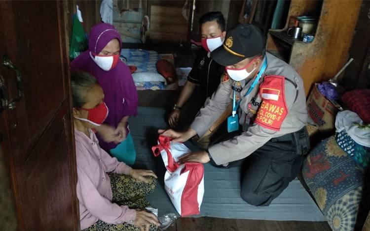 Kapolsek Kahayan Hilir Ipda Widodo saat menyalurkan bantuan sembako dari Presiden kepada warga tidak mampu.