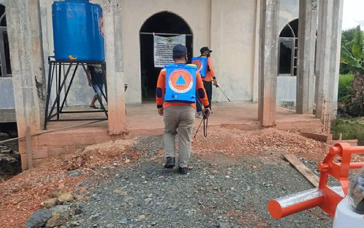 Personel BPBD Kapuas saat menyemprotkan cairan disinfektan di Gereja Saka Kehu.