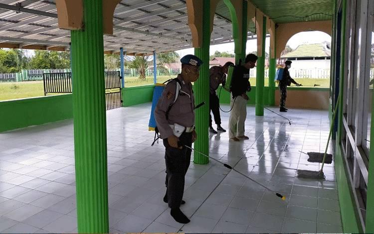 Personel Polsek dan Koramil Danau Sembuluh melakukan penyemprotan cairan disinfektan.
