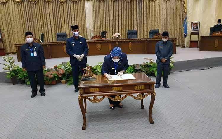 Ketua DPRD Barito Utara, Hj Mery Rukaini saat menandatangani berita acara persetujuan bersama tentang Raperda Pertanggungjawaban pelaksanaan APBD tahun 2019.