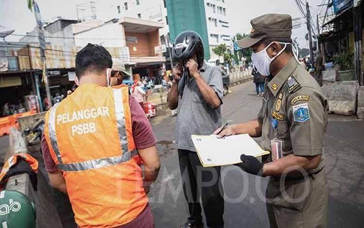Warga menyapu jalan disaksikan petugas Satpol PP setelah melanggar aturan PSBB transisi karena tidak mengenakan masker di kawasan Pasar Minggu, Jakarta, Selasa, 23 Juni 2020. (foto : TEMPO/M Taufan Rengganis)