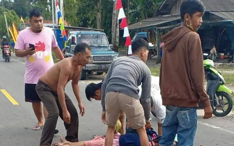 Warga menolong seorang ibu - ibu pingsan setelah terlibat kecelakaan di Jalan Pasir Panjang.