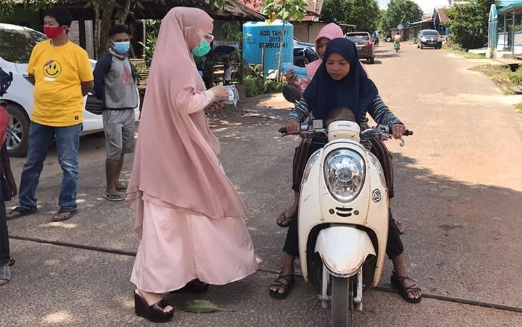 Wakil Bupati Seruyan Hj Iswanti membagikan masker untuk warga Desa Sembuluh.