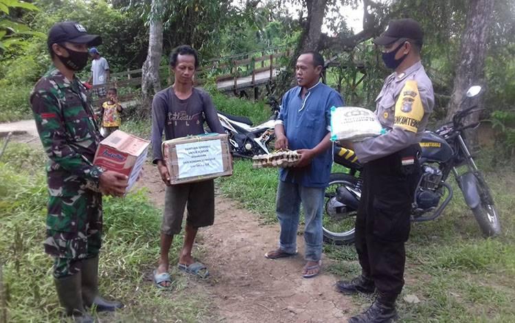 Personel Polsek Kahayan Hilir dan Koramil Bahaur saat menyerahkan bantuan kepada korban kebakaran.