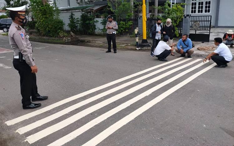 Sejumlah aparat kepolisian bersama Dinas Perhubungan saat memasangrumble strip, untuk mencegah aksi balap liar.