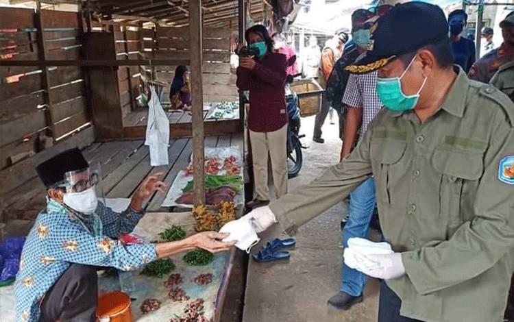 Wakil Ketua Gugus TugasRejikinnor membagikan masker dan sosialisasi kepada pedagang pasar di Kelurahan Muara Laung. (Foto Trisno)