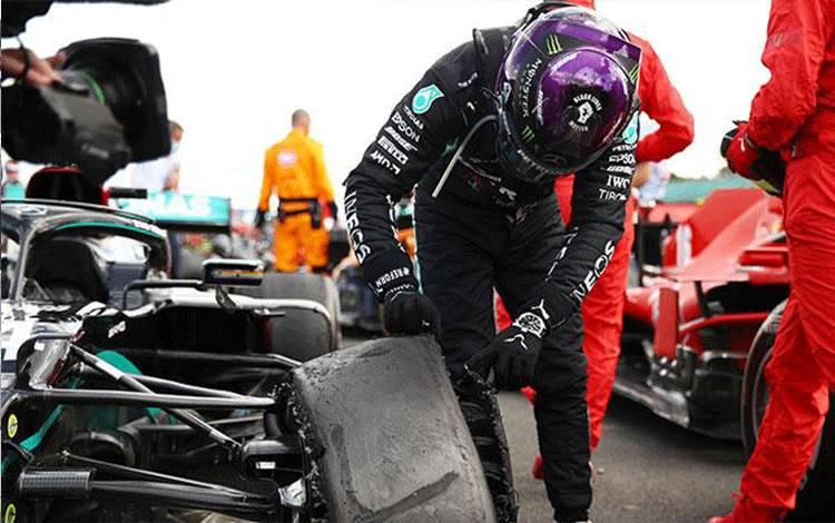 Pembalap Mercedes Lewis Hamilton menunjukkan bannya setelah memenangkan balapan dengan bannya yang mengalami kerusakan pada putaran terakhir F1 GP Inggris, di Sirkuit Silverstone, Ahad, 2 Agustus 2020. Kemenangan itu adalah yang ke 87 dalam karir F1 Hamilton. REUTERS/Bryn Lennon