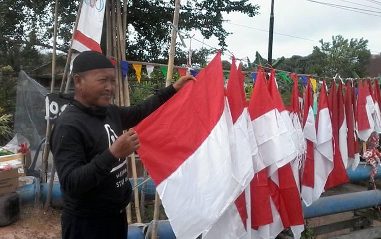 Surya, penjual bendera merah putih dan umbul-umbul menunggu pembeli.