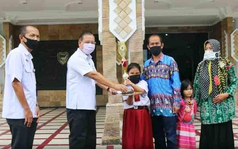 Sekda Barito Utara, Jainal Abidin menyerahkan piala kepada murid SDN Tumpung Laung I yang meraih Juara Harapan I Lomba Bercerita tingkat Provinsi Kalimantan Tengah, Rabu, 5 Agustus 2020.