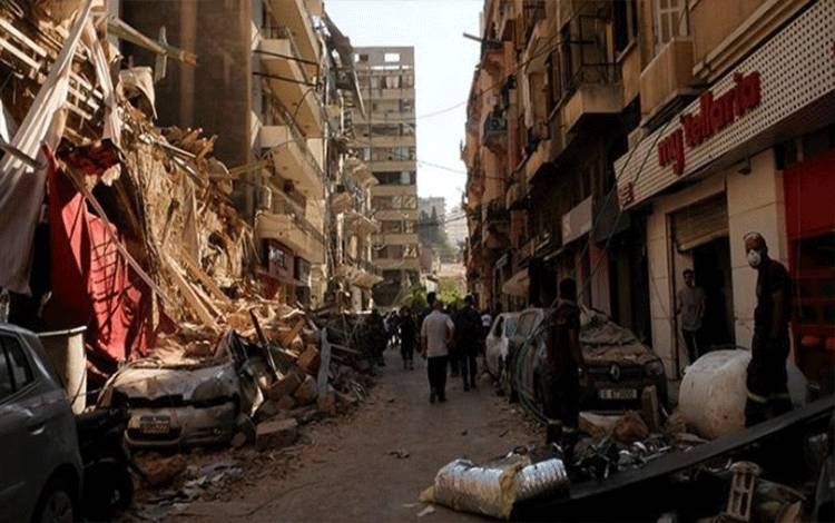 Sejumlah warga melintas di antara bangunan yang rusak akibat ledakan di pelabuhan Beirut, Lebanon, 5 Agustus 2020. REUTERS/Carmen Yahchouchi