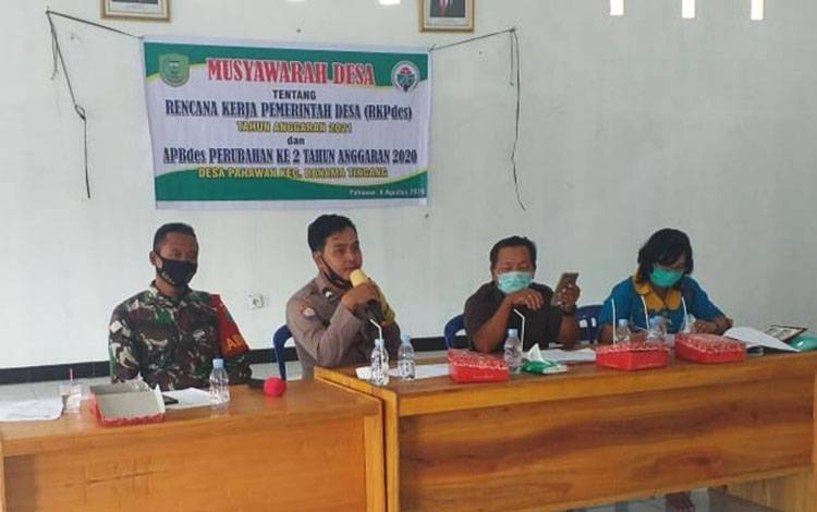 Bhabinkamtibmas Polsek Banama Tingang saat menghadiri Musyawarah RKPDes Pahawan.