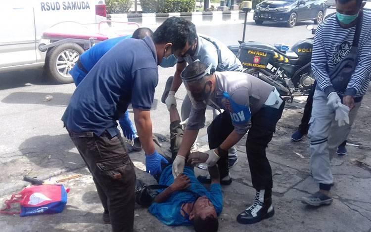 Sejumlah anggota polisi saat mengevakuasi seorang pria yang tergeletak di tepi Jalan HM Arsyad.