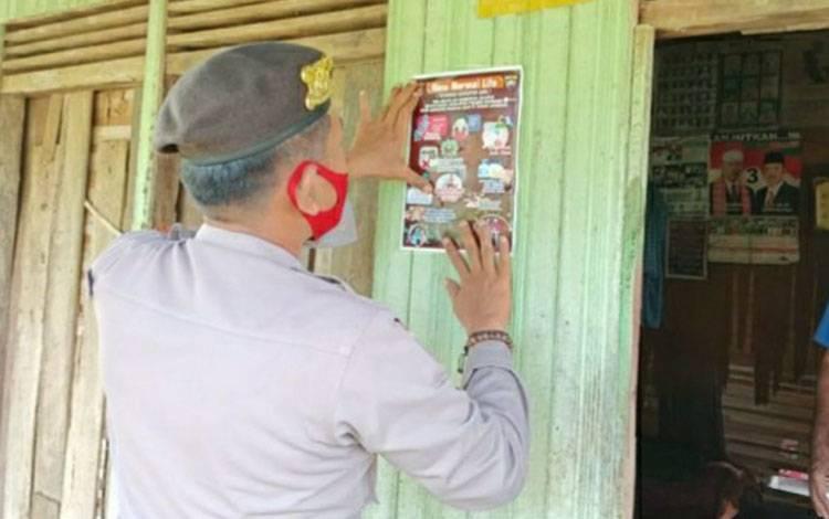 Personel Satbinmas Polres Kapuas saat memasang stiker imbauan pencegah covid-19 di Kecamatan Selat.