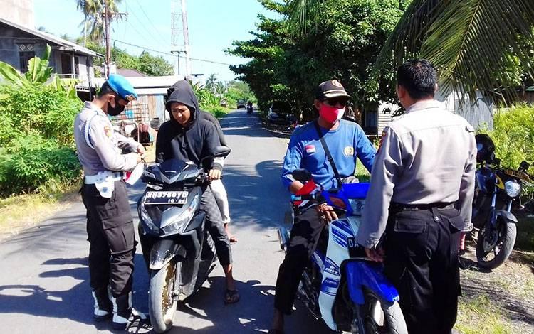 Personel Polsek Kahayan Kuala saat membagikan bendera merah putih kepada masyarakat.