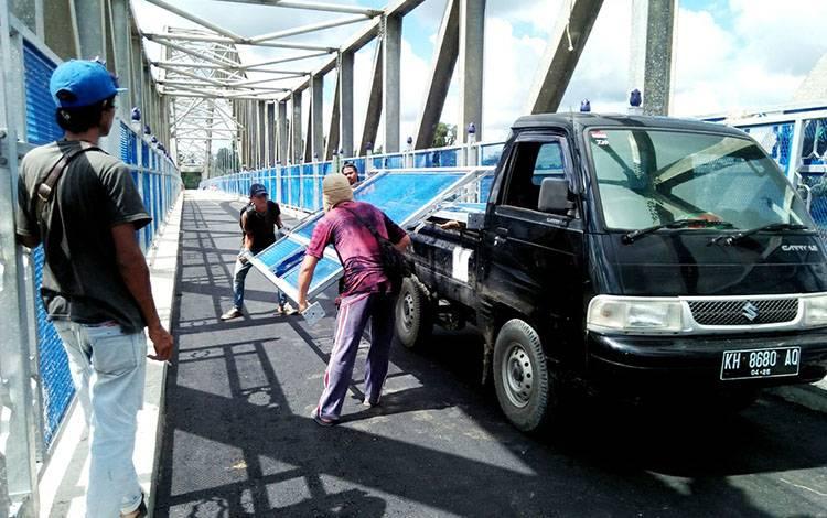 Pekerja saat akan memasang pengaman jembatan penyeberangan Muara Teweh - Jingah.
